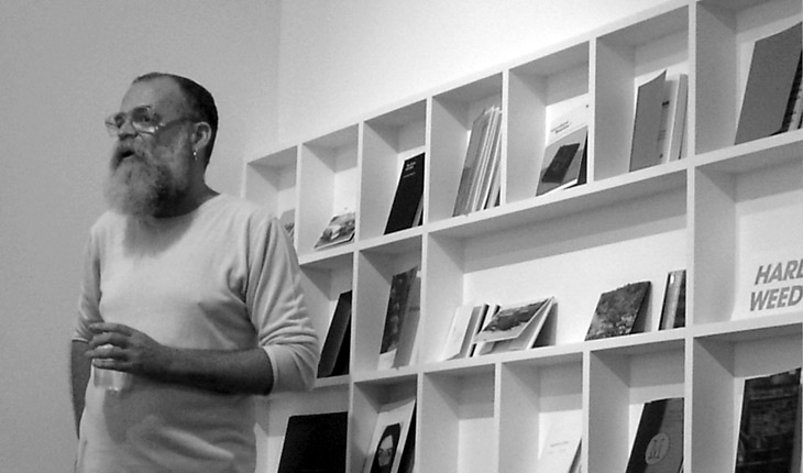 AA Bronson speaking at his exhibition Learn to Read Art: A History of Printed Matter at Artspeak, Vancouver.
